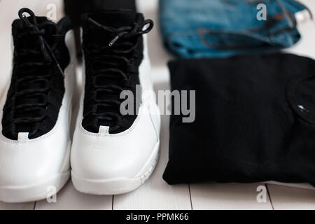 Fashionable men's summer style set of clothes. Denim pants with t-shirts and sneakers on the wooden floor