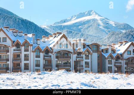 Wooden chalet, houses and snow mountains landscape panorama in bulgarian ski resort Bansko, Bulgaria - Stock Photo