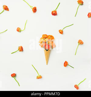 Waffle cone with orange buttercup flowers over white background, flat-lay - Stock Photo