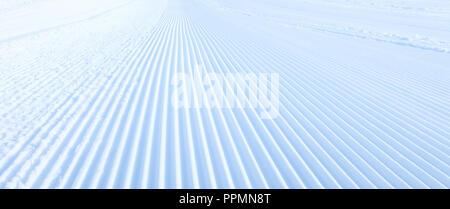 Close-up groomed snow at ski resort, slope banner background texture