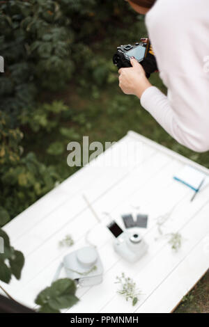 Professional photographer makes photos for the stock. Girl taking pictures of subjects on a white background. - Stock Photo