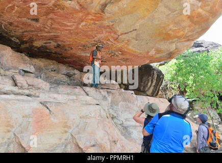 Aboriginal guide pointing out artwork in a rock art gallery on Injalak Hill, Arnhem Land, Northern Territory, Australia - Stock Photo