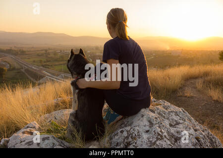 Woman and Siberian husky sitting on a rock and watching the sunset from a summit - Stock Photo