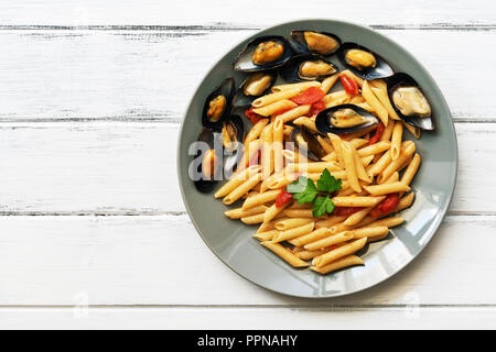Penne pasta with mussels on a white wooden rustic table. Top view, copy space - Stock Photo