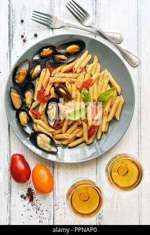 Penne pasta with mussels, tomatoes and white wine on a white wooden rustic background. Top view,flat lay. Mediterranean food