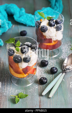 Delicious dietary dessert with curd cream blueberries and peach, sprinkled with sugar powder and decorated with mint leaves. Green rustic background.  - Stock Photo