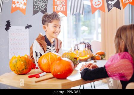 Beaming funny boy wearing Halloween skeleton costume talking to his friend - Stock Photo
