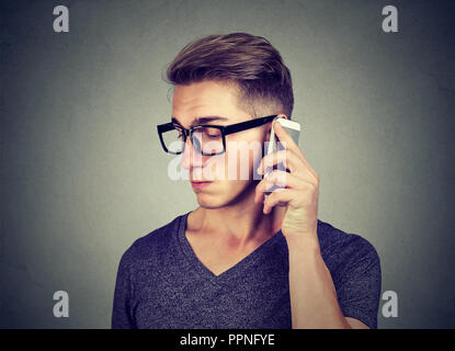 Young man receiving bad news on smartphone while speaking with emotion of sadness - Stock Photo