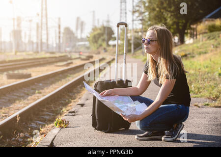 Woman on railway station searching in map for next destination - Stock Photo