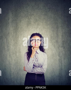 Young brunette woman in eyeglasses looking up in contemplation on gray background - Stock Photo