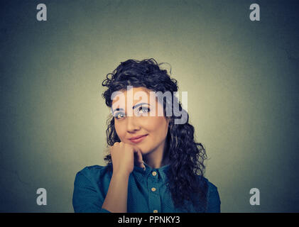 Beautiful curly woman holding touching chin and looking up in happy daydreams on gray background - Stock Photo