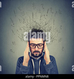 Closeup sad young man with worried stressed face expression and brain melting into lines question marks. Obsessive compulsive, adhd, anxiety disorders - Stock Photo