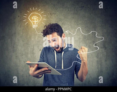portrait of handsome young man with tablet computer having bright financial ideas - Stock Photo