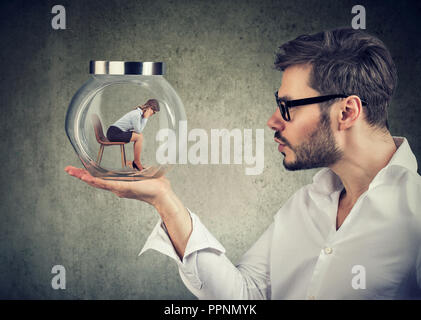 Businessman holding a glass jar with a young sad businesswoman trapped in it - Stock Photo