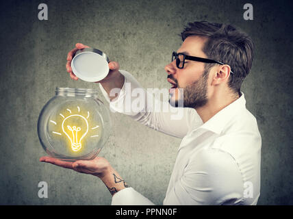 Excited man holding opening a glass jar with bright idea lighbulb inside being creative - Stock Photo