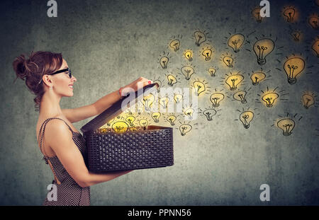 Side view of young happy woman holding a box with brilliant ideas spreading knowledge - Stock Photo