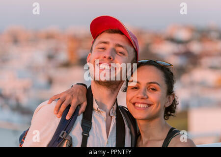 Young woman and young man looking happily at the camera, couple, Plaza de la Encarnacion, Seville, Andalusia, Spain - Stock Photo