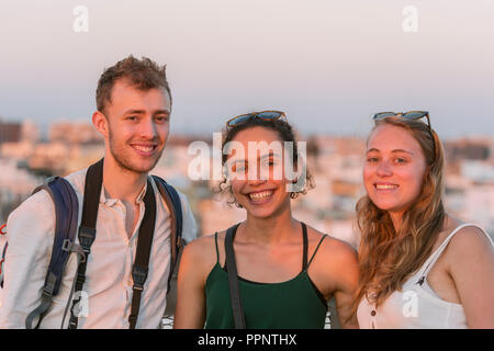 Two young women and young man looking into the camera, friends, Plaza de la Encarnacion, Sevilla, Andalusia, Spain - Stock Photo
