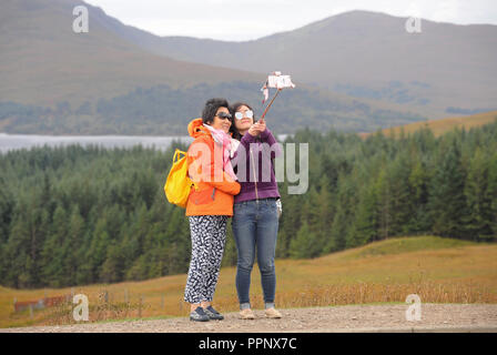 JAPANESE TOURISTS TAKING SELFIE PHOTOGRAPHS IN THE SCOTTISH HIGHLANDS RE TOURISM TOURING COACH TOURS HOLIDAYS VIEWPOINT SCENIC VIEWS UK - Stock Photo