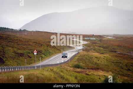 CARS TRAVELLING ON THE A835 NEAR ULLAPOOL SCOTLAND RE BENDS IN ROAD THE HIGHLANDS DRIVING REMOTE LOCATIONS WET ROADS SCOTTISH UK - Stock Photo