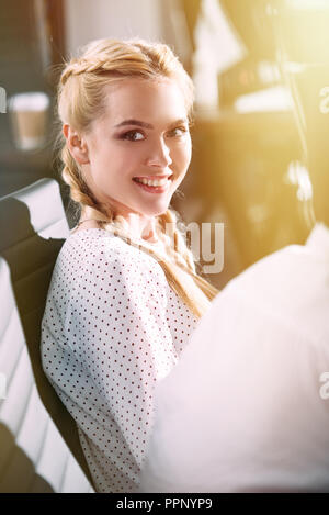 smiling young businesswoman sitting on chair and looking at camera in modern office - Stock Photo