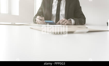 Businessman or banker working with a manual calculator on balancing his books in a low angle view over the desk of his hands with foreground copy spac - Stock Photo