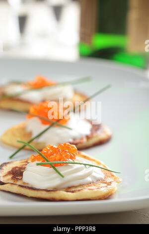 Blinis with red caviar on a plate - Stock Photo