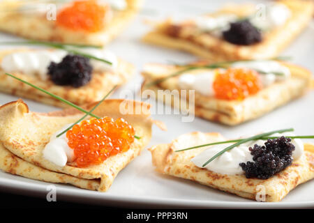 Crepes with red and black caviar on a plate - Stock Photo