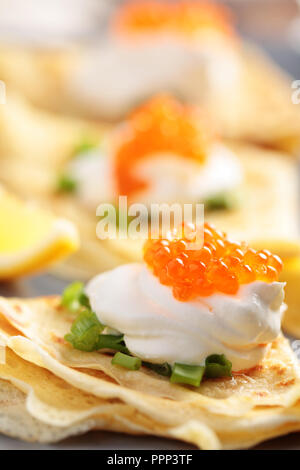 Crepes with red caviar on a plate - Stock Photo