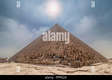 The Pyramid of Cheops illuminated by the sun in backlight, with people entering inside to visit it. The area with the great pyramids of Giza, Egypt - Stock Photo