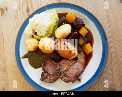 English lunch  dinner meal lamb chops roast potatoes cauliflower roasted carrots red wine gravy and mint sauce blue edge white plate on a wooden table - Stock Photo