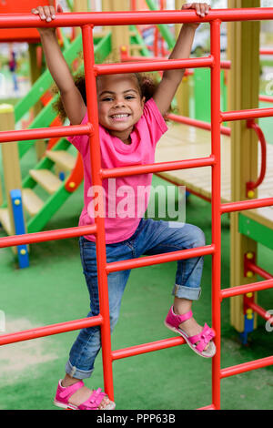 happy curly african american little child climbing on stairs at playground - Stock Photo