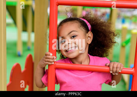 smiling curly african american little child climbing on stairs at playground - Stock Photo