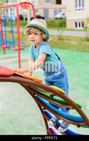 adorable little boy in panama climbing on stairs at playground - Stock Photo