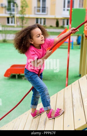 side view of curly african american little child climbing with rope at playground - Stock Photo