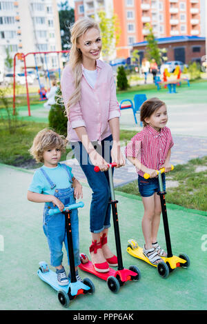 happy mother riding on kick scooters with adorable son and daughter at playground - Stock Photo