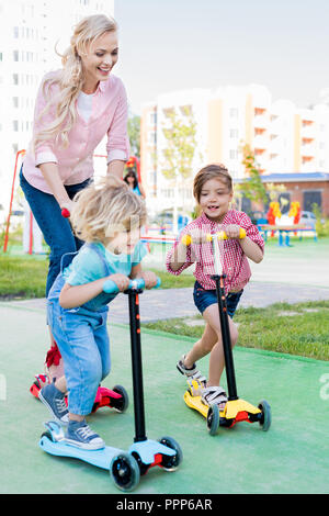 selective focus of mother riding on kick scooters with son and daughter at playground - Stock Photo