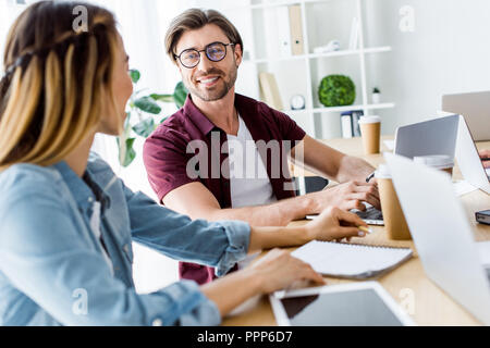 smiling colleagues working on startup project in office and looking at each other - Stock Photo