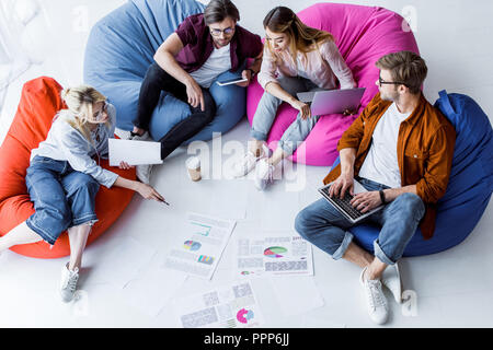 high angle view of multicultural colleagues discussing startup project in office - Stock Photo