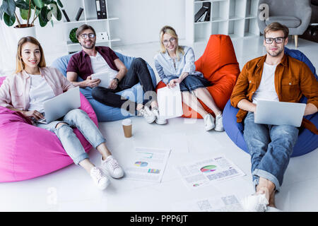 multicultural colleagues working on startup project in office and sitting on bean bag chairs with gadgets - Stock Photo