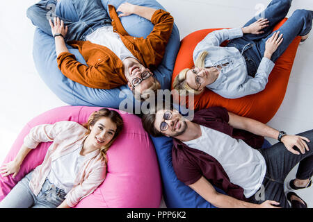 top view multicultural colleagues of startup project lying on bean bag chairs in office - Stock Photo