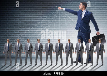 Boss employee manipulating his staff in business concept - Stock Photo