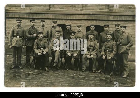 German historical photo: group portrait of a military unit, the soldiers and the officer smoke cigarettes, against a brick wall. world war one 1914-18 - Stock Photo