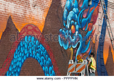 The UTI crew at work on a new mural on Alameda near 4th Place in the Downtown Los Angeles Arts District in Los Angeles, CA, USA - Stock Photo