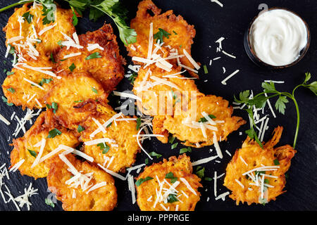 Top view on pumpkin pancakes with grated parmesan cheese, seasoned with chopped parsley served with sour cream sauce on a black stone board, on a blac - Stock Photo