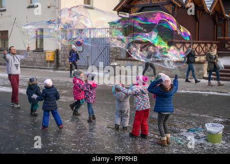 Karpacz, Poland - February 2018 : Children trying to catch giant soap bubbles on the main high street in Karpacz town, polish winter ski resort - Stock Photo