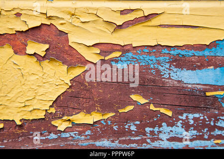 Old peeling paint on the board. Blue and orange background. - Stock Photo