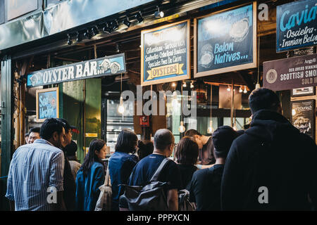 London, UK - September 17, 2018: Customer queuing at an oyster bar in Borough Market, one of the largest and oldest food markets in London. - Stock Photo