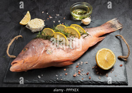 Freshly marinated raw Red snapper fish with lemon slices, garlic and rosemary herbs, on dark background - Stock Photo