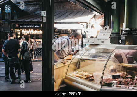 London, UK - July 24, 2018: Customer looking at cheeses at a stand in Borough Market, one of the largest and oldest food markets in London. - Stock Photo